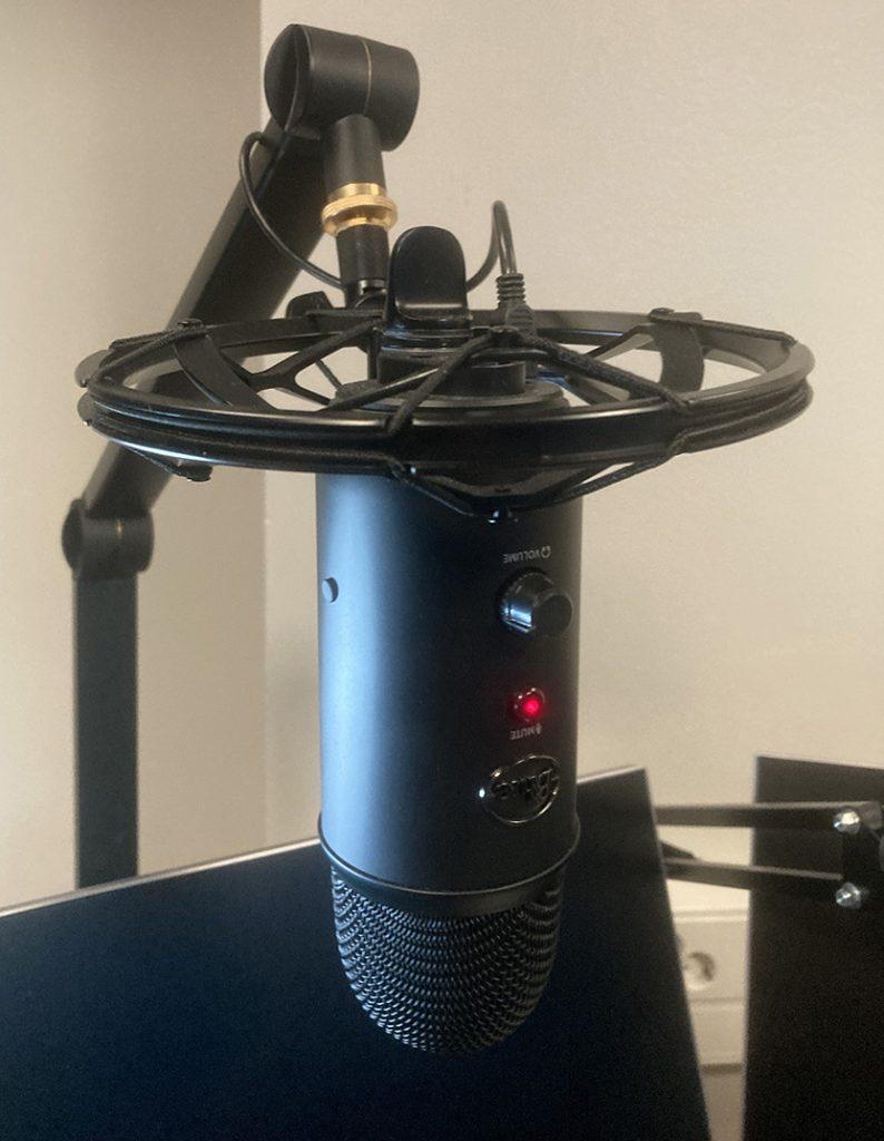 Podcastin tallennus tietokoneeseen liitetyllä Yeti-mikrofonilla.