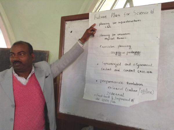 """Viimeinen workshop, mies osoittaa flappipaperilla lukevaa """"Future plan for science ed""""-tekstiä."""