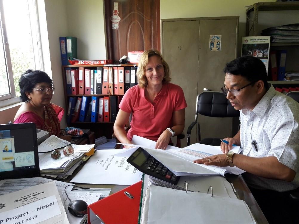 Projektin hallinnollisesta työstä vastaavia henkilöitä talousraporttien äärellä Nepalissa.