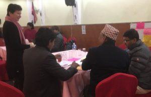Nepalilaisia kumppaneita työskentelemässä. Seija Koskela ohjaa kirjoittamistyötä pöydän vierellä.