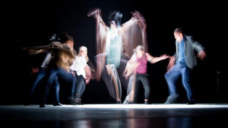 modernin tanssin esitys, vauhdikkaasti liikkuvia henkilöitä mustalla taustalla