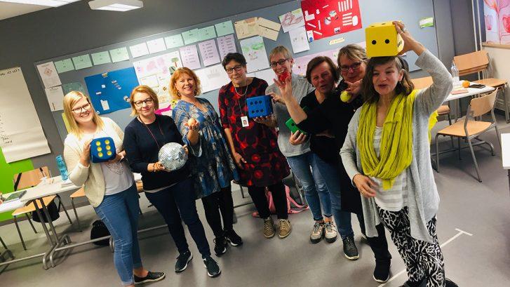 Valma-opettajia Keravalla luokkatilassa. He pitelevät käsissään suuria arpakuutioita.