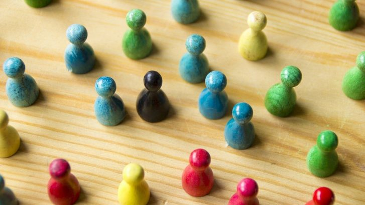 Eri värisiä lautapelinappuloita puisella alustalla