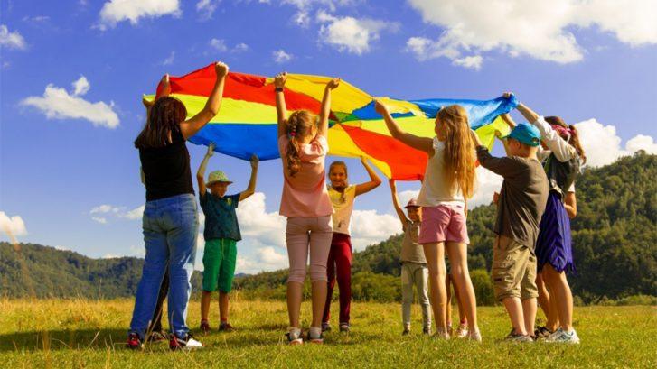 Ulkotilassa nurmikolla iso ryhmä koululaisia nostaa ilmaan värikästä varjoa.