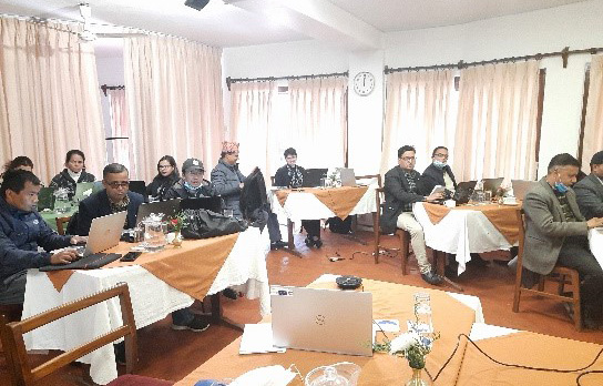Project's specialists and workers sitting and working in a meeting room with laptops on the tables.