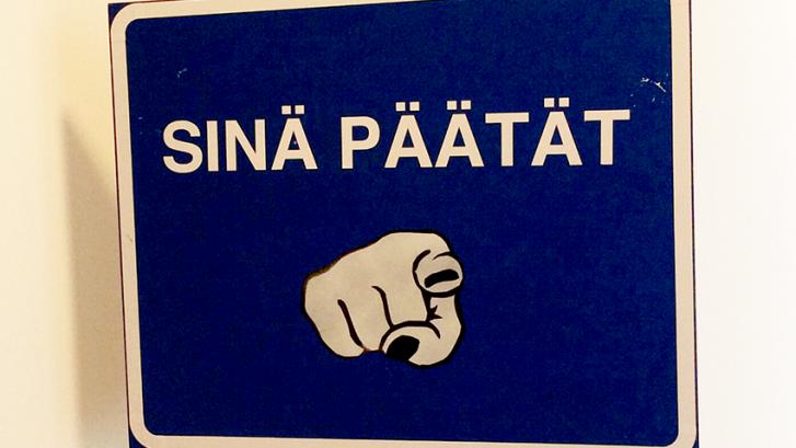 """Kyltti, jossa teksti """"sinä päätät"""" ja kohti osoittava sormi."""
