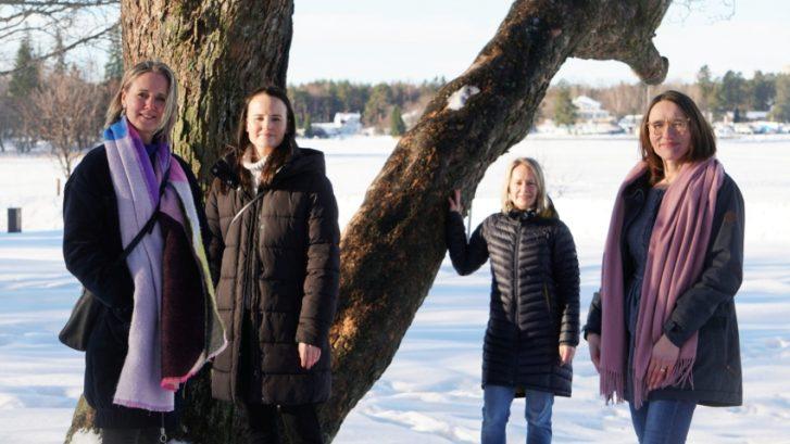 Människor som står runt ett träd.