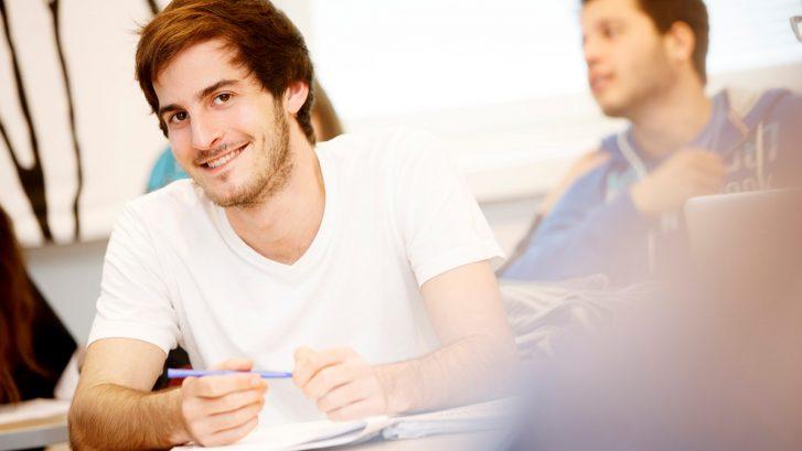 Kuvituskuvassa etualalla hymyilevä nuori mies.