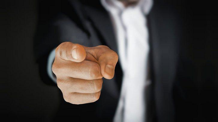 pukumies osoittaa sormella lukijaa