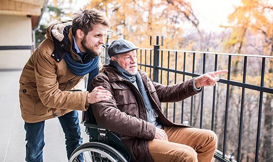 Mies ja vanhus, joka on pyörätuolissa.