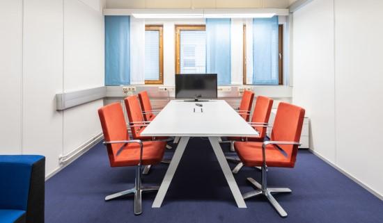 DGC:n kokoushuone pöydällä, näytöllä ja kuudella tuolilla